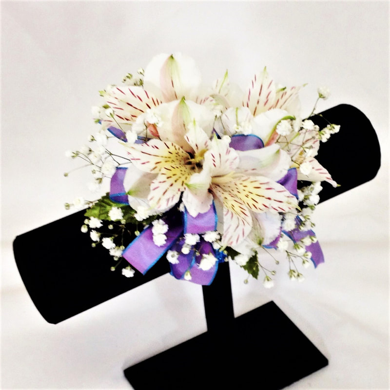 White Alstro corsage with Periwinkle Bow