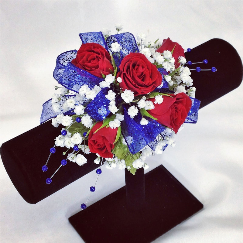 Red rose corsage with royal blue bow