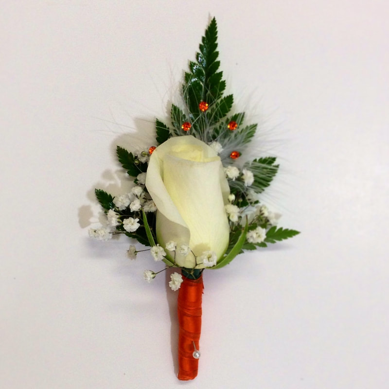 White rose bout with orange wrap and rhinestones