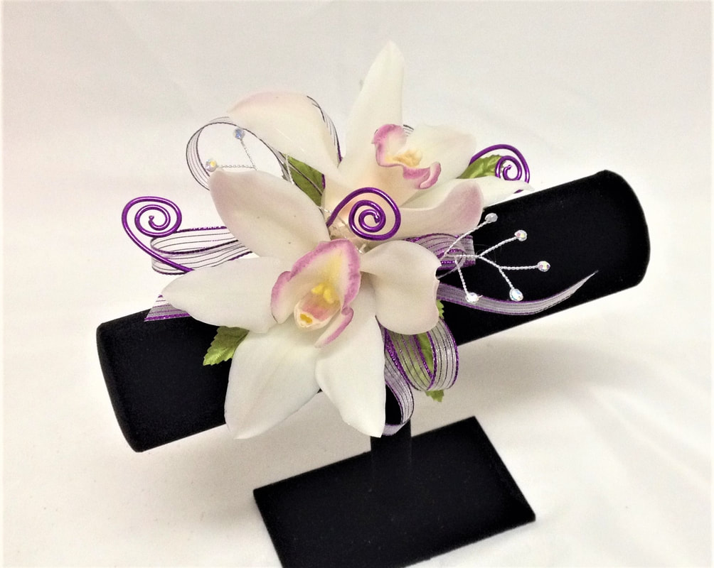 White orchid corsage with purple bow