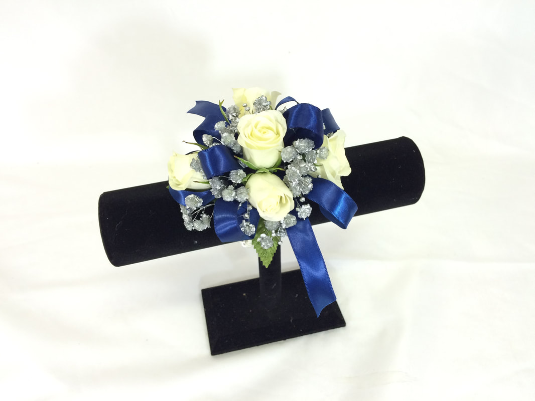 White rose wristlet with silver babies breath and dark blue bow