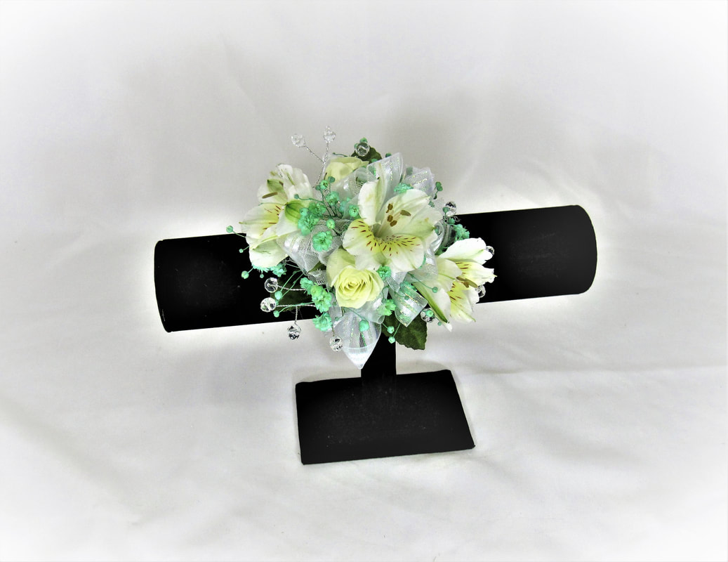 White alstro corsage with mint babies breath