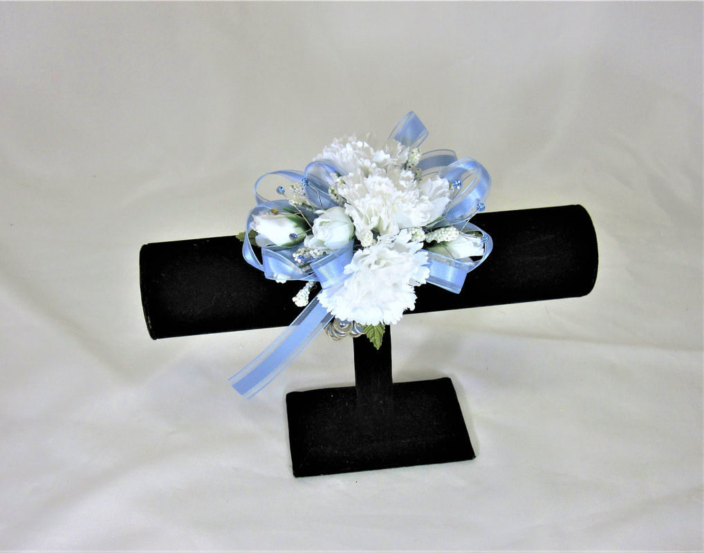 White carn corsage with light blue bow