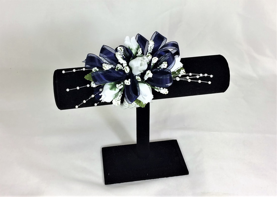White spray rose corsage with navy bow