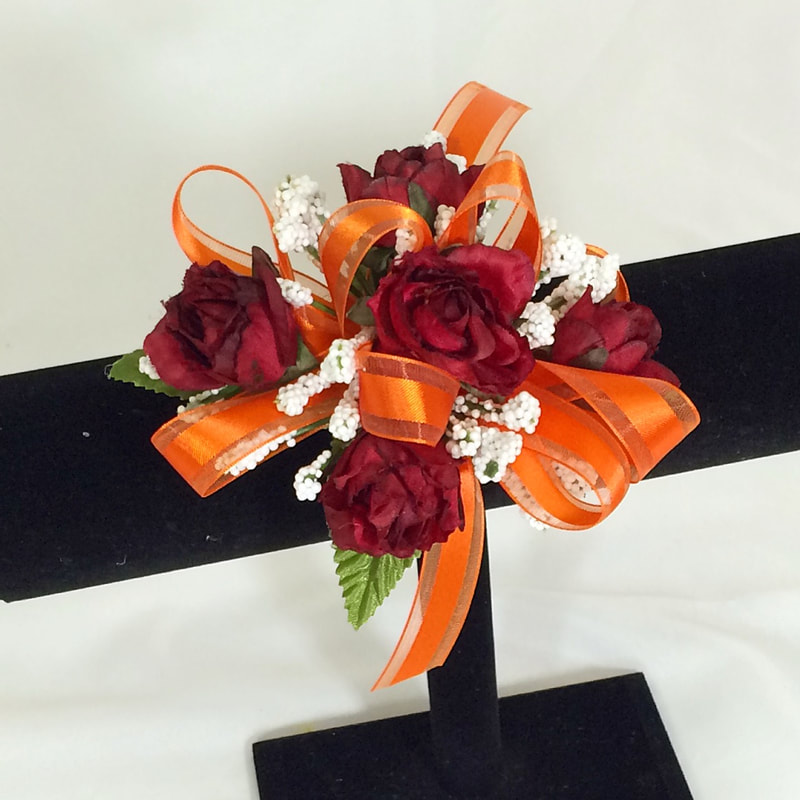 Burgundy rose corsage with orange bow
